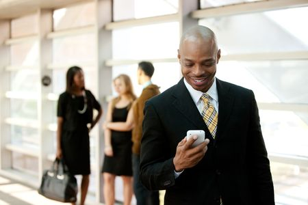 american content: A business man with a smart phone and co-workers in the background Stock Photo