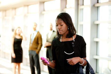 celulas humanas: Una mujer de negocios con un tel�fono inteligente con colegas en segundo plano