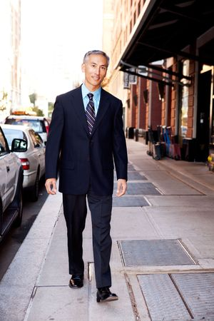 An asian looking business man walking in a street Stock Photo - 6052876