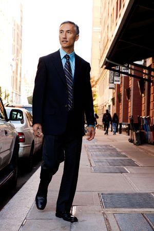 sidewalk: A business man in a city setting on a sidewalk
