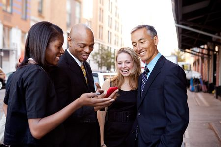 A group of business people looking at a cell phone and laughing Stock Photo - 6053462