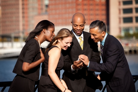 A group of business people crowded around a cell phone Stock Photo - 6053478