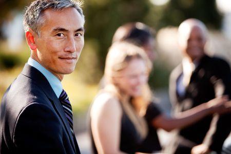 Un groupe de gens d'affaires à l'extérieur - mise au point nette sur l'homme asiatique au premier plan