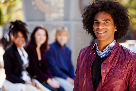 Group of four people of different ethnicities with one man as focus of image. Horizontally framed shot. photo