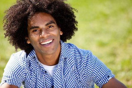 Young man smiling at camera in a park. Horizontally framed shot. photo