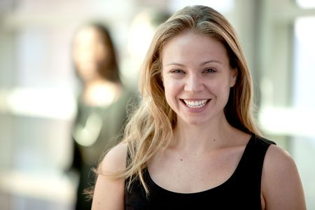 Attractive young blonde woman smiling while looking at camera with woman in background. Horizontally framed shot. photo