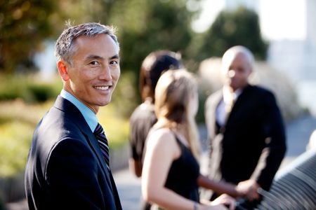 четыре человека: Group of four people with one man as focus. Horizontally framed shot. Фото со стока