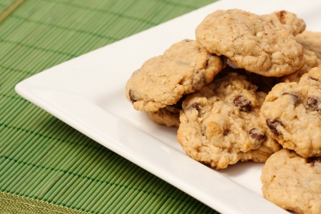 A plate of oatmeal chocolate chip cookies on a green mat photo