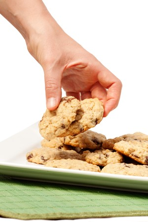 A plate of oatmeal chocolate chip cookies with a hand taking two. photo