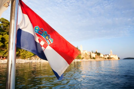 A croatian flag in front of a landscape of the island of Rab photo