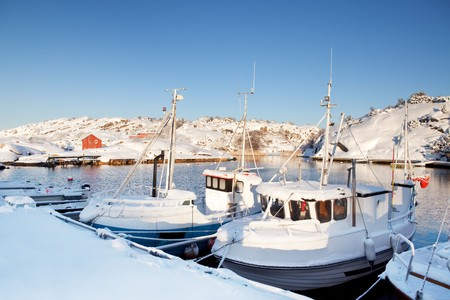 fredrikstad: A dock in southern Norway with boats covered in snow