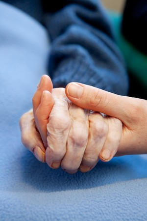 visit: A young hand touches and holds an old wrinkled hand