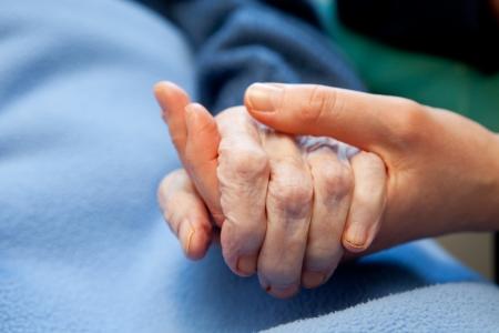 Een jonge hand raakt en bezit een gerimpelde oude hand Stockfoto
