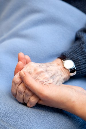 An old handing holding a young hand.  Shallow depth of field with focus on the hands. photo