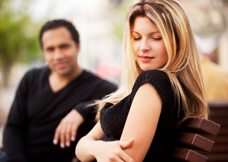get: A man and woman sitting on a bench, the woman looking sky