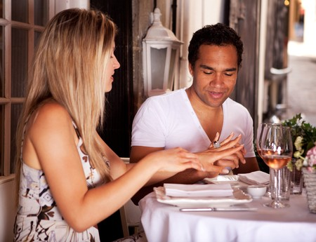 A man giving a woman a ring in an outdoor cafe in France, Europe Stock Photo - 7652982
