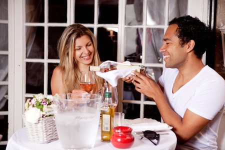 A happy couple sharing a bottle of wine in an outdoor cafe in Europe Stock Photo - 7652987