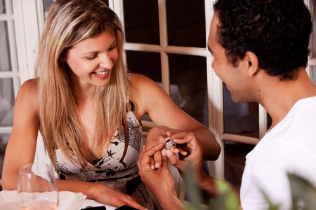 A man giving a ring present on a date in an outdoor cafe Stock Photo - 7653037