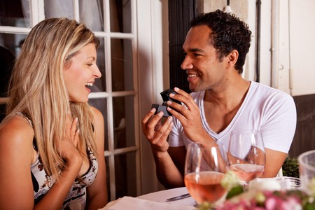 A man giving a ring as a gift to a female in an outdoor cafe Stock Photo - 7652980
