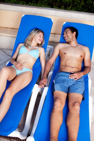 A happy couple lounging in pool chairs photo
