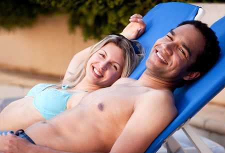 A happy couple looking at the camera relaxing in pool side chairs photo