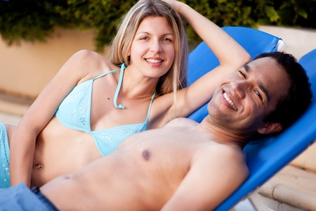 A happy couple on beach chairs, looking at the camera Stock Photo - 7629891