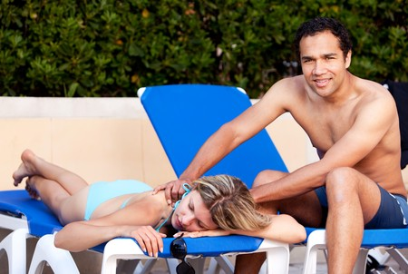 A couple relaxing by the pool, the man giving the woman a back massage Stock Photo - 7630434