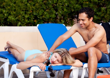 A woman receiving a back massage on a pool chair photo