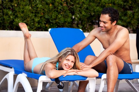 A man giving a back massage to a woman on a beach chair Stock Photo - 7630395