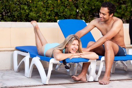 A happy couple relaxing beside a pool. Stock Photo - 7630317