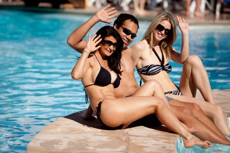 greeting people: A group of friends on a holiday at a hotel pool waving to the camera