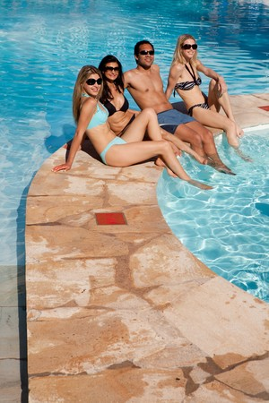 A group of friends relaxing at and outdoor hotel pool photo