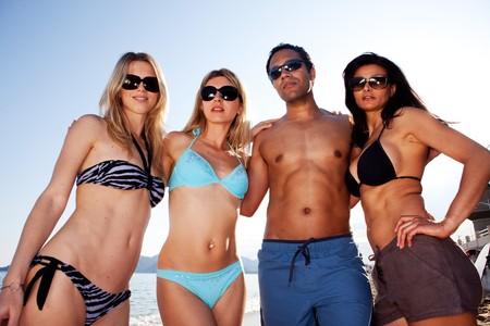 personas banandose: Un grupo de amigos en la playa con un abrazo de grupo