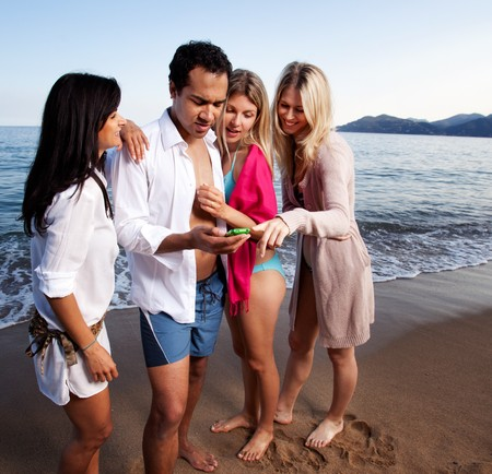 A group of friends looking at a cellphone at the beach photo