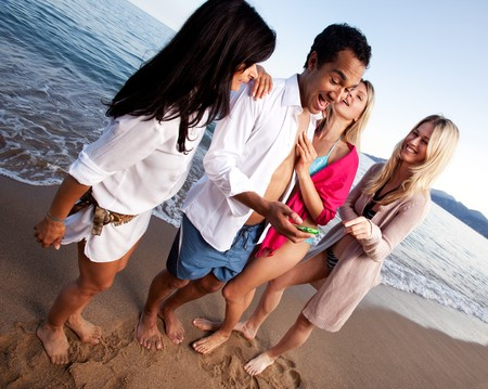 A group of friends having fun at the beach, looking at a cellphone photo
