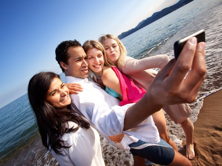 A group of young adults taking a self portrait with a cell phone photo