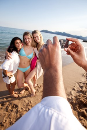 A person taking a picture of three women with a camera phone.  Shallow depth of field, focus on camera photo