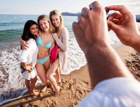 A group of women having their picture taken by a camera phone.  Shallow depth of field, focus on women. photo