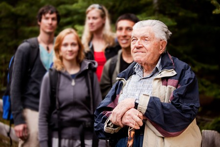80 85: An elderly man giving a tour for a young group of people