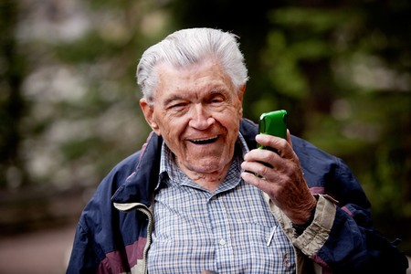 80 85: An old man laughing and smiling with a cell phone. Stock Photo