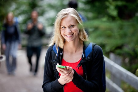 people on phone: A happy woman holding a smart phone, looking at the camera Stock Photo