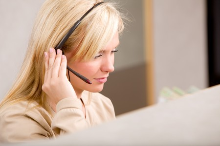 A receptionist talking on the phone with a headset Stock Photo - 7630272