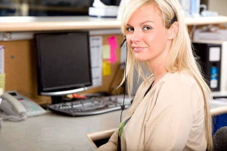 medical assistant: A medical receptionist at a desk with a phone headset Stock Photo