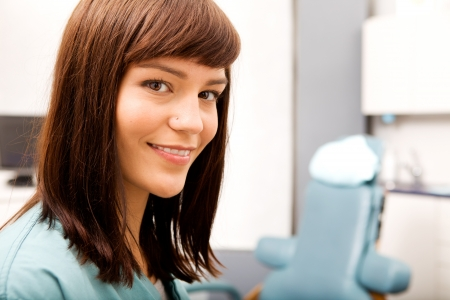 A portrait of a dental hygienist in front of a dental chair Stock Photo - 7630437