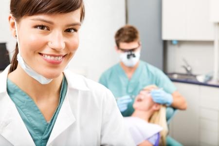 Un retrato de una asistente dental sonriendo a la cámara con el dentista trabaja en segundo plano