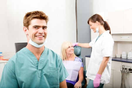 A happy smiling dentist at a clinic with an assistant and patient photo