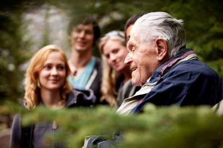 An elderly man telling stories to a group of young people photo