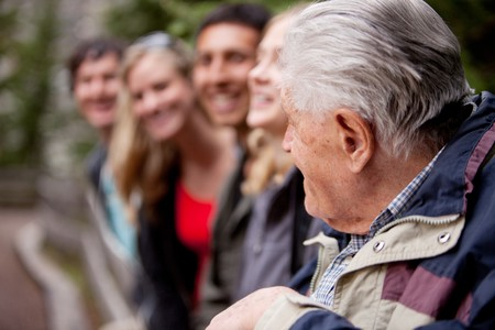 An elderly man guiding a group of young people in the forest Stock Photo - 7683031