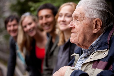 An elderly man telling stories to a group of young people in the forest Stock Photo - 7690850