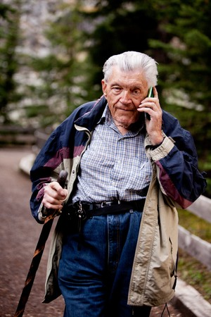 A senior talking on a cell phone outdoors in the forest photo